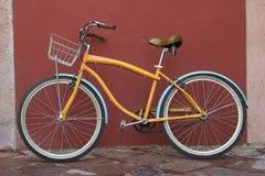 Uma bicicleta em uma rua sobre a parede vermelha Imagem de Stock Royalty Free