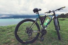Uma bicicleta está em um gramado verde da costa de mar com uma ideia do conceito da cordilheira da recreação ativa e de lifes sau fotografia de stock royalty free