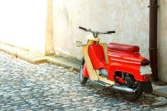 Uma bicicleta motorizada vermelha está pela parede no pavimento da cidade velha imagem de stock royalty free