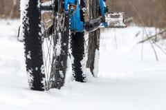 Uma bicicleta que levanta-se no fim da neve Flocos da neve que flutuam em pneus fora de estrada escuros Tempo do inverno no campo Imagem de Stock
