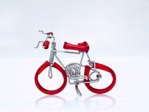 Uma bicicleta vermelha diminuta no fundo branco na vista superior Foto de Stock