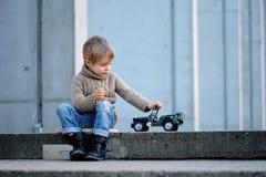 Uma BO que senta-se nas etapas e que joga um carro militar do brinquedo fotografia de stock