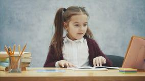 Uma boa estudante senta-se na tabela em um fundo cinzento Durante este tempo, toma a pena e começa a escrever uns trabalhos de ca vídeos de arquivo