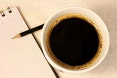 Uma bobina quente preta de suportes do café ao lado de um bloco de notas com uma pena foto de stock royalty free