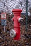 Uma boca de incêndio vermelha está na frente de uma cerca imagem de stock