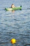 Uma boia de advertência amarela no lago, barco de enfileiramento no fundo Imagem de Stock Royalty Free