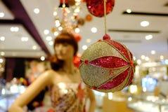 Uma bola bonita do ornamento que pendura do teto de construção com borrado um manequim da mulher imagem de stock