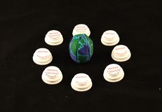 Uma bola com o globo nela cercou por tampas da garrafa da prescrição em um fundo preto Imagem de Stock