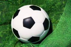 Uma bola de futebol branca com uma rede preta do objetivo na rede do objetivo Os campeonatos mundiais, europeu patrocinam a liga Imagem de Stock Royalty Free