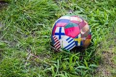 Uma bola de futebol com um teste padrão sob a forma das bandeiras de países diferentes na grama foto de stock