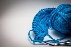 Uma bola do fio azul em um fundo branco com agulhas de confecção de malhas foto de stock royalty free