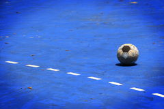 Uma bola velha em um campo azul do cimento Foto de Stock