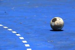 Uma bola velha em um campo azul do cimento Imagem de Stock Royalty Free