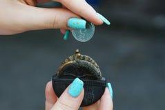 Uma bolsa aberta do preto pequeno e uma moeda nas mãos de uma menina imagem de stock royalty free