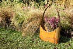 Uma bolsa f?mea oxidada do metal com borlas e uma flor da urze em um fundo da grama amarela Projeto da casa e do jardim fotografia de stock royalty free