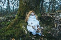 Uma boneca assustador ceepy, sentando-se em uma floresta no inverno Com uma obscuridade, abafada edite imagem de stock
