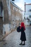 Uma bruxa pequena em um vestido preto com cabelo vermelho Fotos de Stock Royalty Free