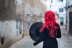 Uma bruxa pequena em um vestido preto com cabelo vermelho na rua da cidade velha Imagens de Stock Royalty Free