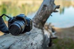 Uma câmera de DSLR manteve-se em um log da madeira na natureza aberta fotografia de stock