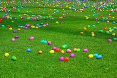 Uma caça do ovo da páscoa com ovos plásticos em um gramado verde fotografia de stock