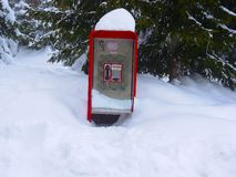Uma cabine de telefone na neve fotos de stock royalty free
