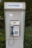 Uma cabine de telefone vazia ou disponível a um parque imagem de stock royalty free