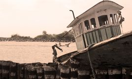 Uma cabine do barco dilapidado do pescador em um porto pequeno indiano imagens de stock