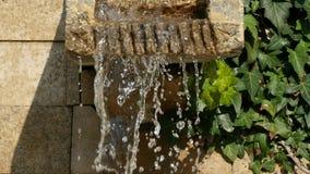 Uma cachoeira artificial pequena nas rochas no parque, água corrente constante, gotejando para baixo, lentamente video estoque