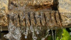 Uma cachoeira artificial pequena nas rochas no parque, água corrente constante, gotejando para baixo, lentamente, o close-up vídeos de arquivo