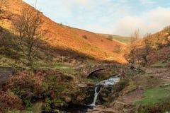 Uma cachoeira outonal e uma ponte de pedra do cavalo de carga em três condados imagens de stock