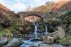 Uma cachoeira outonal e uma ponte de pedra do cavalo de carga em três condados imagem de stock royalty free