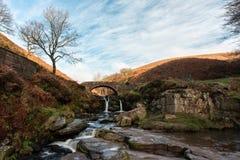 Uma cachoeira outonal e uma ponte de pedra do cavalo de carga em três condados foto de stock royalty free