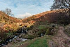 Uma cachoeira outonal e uma ponte de pedra do cavalo de carga em três condados fotos de stock