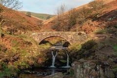 Uma cachoeira outonal e uma ponte de pedra do cavalo de carga em três condados fotografia de stock royalty free