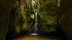 Uma cachoeira pequena entre rochas imagem de stock