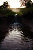 Uma cachoeira pequena que flui em uma associação corroída Fotografia de Stock Royalty Free