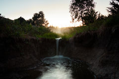 Uma cachoeira pequena que flui em uma associação corroída Fotos de Stock Royalty Free