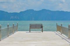 Uma cadeira de madeira na doca Fotos de Stock Royalty Free