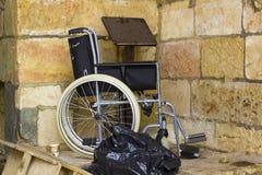 Uma cadeira de rodas saiu em um canto com os desperdícios e no outro detritis em imagens de stock royalty free