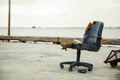 Uma cadeira velha do escritório exterior perto do mar e das sandálias está sob a cadeira imagem de stock