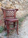 Uma cadeira velha que está ao lado da parede imagem de stock
