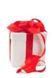 Uma caixa branca amarrada com uma curva vermelha da fita do cetim Fotografia de Stock