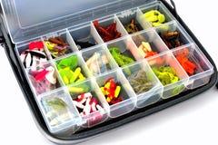 Uma caixa com uma variedade de iscas do silicone encontra-se em um saco da pesca, wh fotos de stock