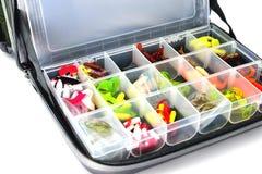 Uma caixa com uma variedade de iscas do silicone encontra-se em um saco da pesca, wh fotografia de stock