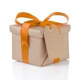 Uma caixa de Natal do presente envolvida com curva de papel e alaranjada Fotografia de Stock Royalty Free