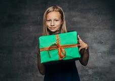 Uma caixa de presente bonita da terra arrendada da moça no tempo do Natal imagem de stock royalty free