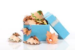 Uma caixa de presente com as sobras de apontar a cera colorida escreve i imagens de stock royalty free