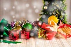 Uma caixa de presente contra uma árvore de Natal no fundo de madeira com neve w Fotografia de Stock Royalty Free