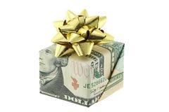 Uma caixa de presente envolvida com o dólar americano decorado com a fita dourada do presente imagens de stock royalty free