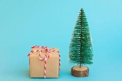 Uma caixa de presente envolvida no papel do ofício amarrado com as árvores de Natal brancas vermelhas da fita no fundo azul Prese imagens de stock royalty free